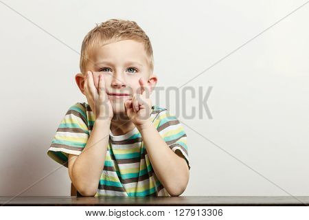 Free time fun and expression. Little boy play indoors make silly gestures face emotions. Blonde child sit hold head with hand.