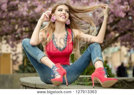 Girl Sitting In A Park With Telephone