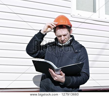 Worker on a construction site looks at the drawing and compares the work done
