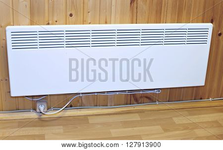 Household wall-mounted electric heater in a wooden house