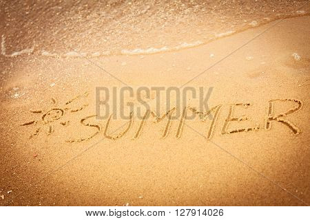 Holidays vacation concept. The word summer written in the sand on beach.