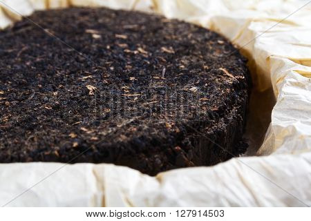 Pu-erh tea on background rice paper close up