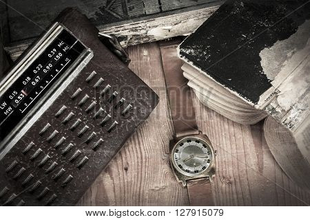 Old russian radio and watch with old books on wooden