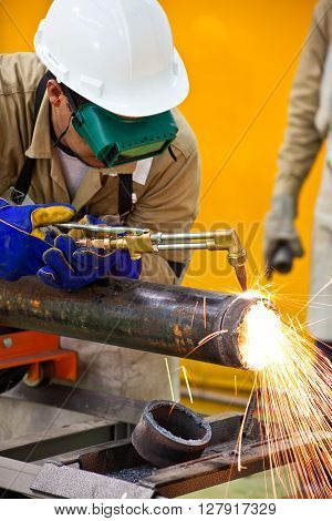 Welder cutting a pipe wearing protective clothes and equipment