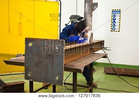 Welding a beam  wearing protective clothes and equipment