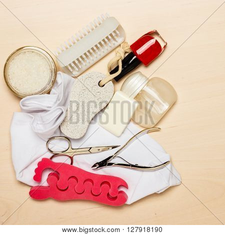 Foot care. Pedicure accessories set tools on wooden board background top view with