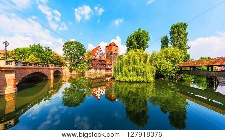 Scenic summer view of the German traditional medieval half-timbered Old Town architecture and bridge over Pegnitz river in Nuremberg Germany
