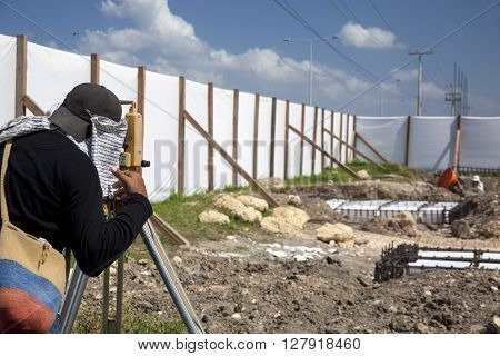 Surveyor looking through the theodolite at a construction field