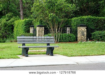 View of park bench / bus stop on road in Naples florida with sidewalk vegetation and stone posts.