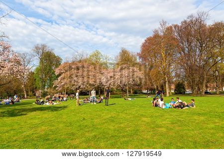 Maastricht Netherlands - April 11 2016: unidentified people lying in a park in Maastricht in spring. Maastricht is a university city and the capital of the Dutch province Limburg