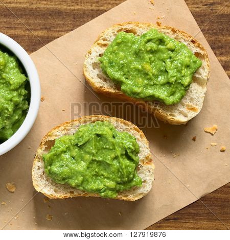 Fresh avocado cream or guacamole on baguette slices photographed overhead with natural light (Selective Focus Focus on the top of the avocado cream)
