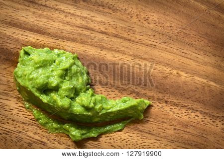 Fresh avocado cream or guacamole photographed overhead on wood with natural light (Selective Focus Focus on the top of the avocado cream)