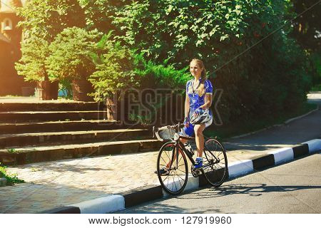 Female sportsman cyclist having rest at the race. Riding racing bicycle. Break, stop at road.  Woman cycling on countryside summer road or highway. Triathlon or cycling competition.