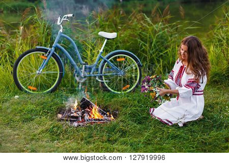 Woman in Folk costume with bicycle. Young attractive woman at riverside having rest with bicycle in national ethnic ukrainian folk traditional dress. Girl looking at circlet of flowers near bonfire.
