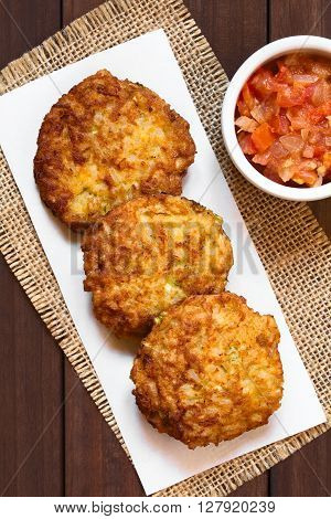 Rice patties or fritters made of cooked rice carrot onion garlic and celery stalks with tomato sauce on the side photographed overhead with natural light