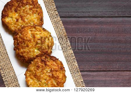 Rice patties or fritters made of cooked rice carrot onion garlic and celery stalks photographed overhead on dark wood with natural light