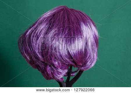 Artificial wig with purple hair on a green background