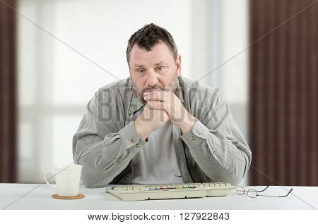 Sad middle-aged man is sitting at white desk. The bearded man wears a grey shirt. There are white cup keyboard glasses and window unfocused background. Horizontal indoors picture
