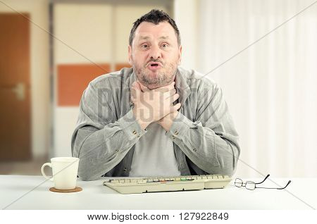 Portrait of middle-aged man is reached at the point of stressing out. The man is creaming with hands on his neck. He sits at white desk. There are grey keyboard white cup and glasses on it. Horizontal indoors picture