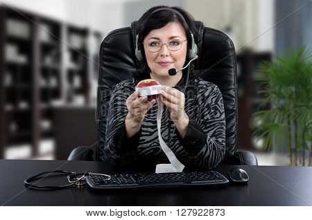 Glasses dietitian in headset shows how to measure body waist using an apple for example. Middle-aged woman sits at black table in small office. She wears headset because working online. Horizontal indoors picture