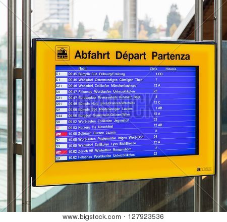Bern Switzerland - 19 October 2015: departure board mounted on a transparent wall at one of the entrances of the Bern train station. The city of Bern is the capital of Switzerland and also the capital of the Swiss canton of Bern.