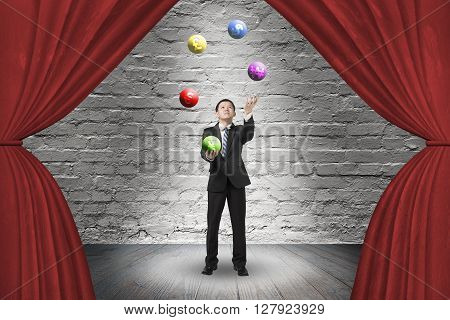 Businessman Juggling With Currency Symbol Balls On Red Curtain Stage
