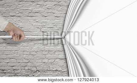 Hand Pulling Down White Curtain Covering Old Brick Wall