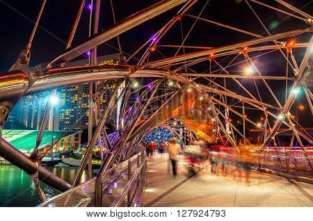 Night view of Helix pedestrian bridge in Marina Bay in Singapore. It is a part of the walkway around Marina Bay. Blurred people walking inside