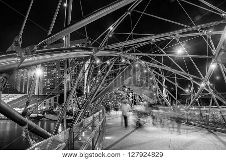 Night view of Helix pedestrian bridge in Marina Bay in Singapore. It is a part of the walkway around Marina Bay. Blurred people walking inside. Black and white