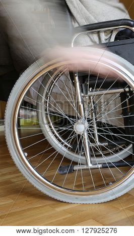motion of hand of the young disabled in the wheel of the wheelchair