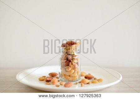 Mix of nuts in the glass jars and plate on the table ** Note: Shallow depth of field