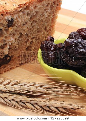 Fresh baked wholemeal bread heap of dried plums and ears of wheat lying on cutting board concept for healthy eating