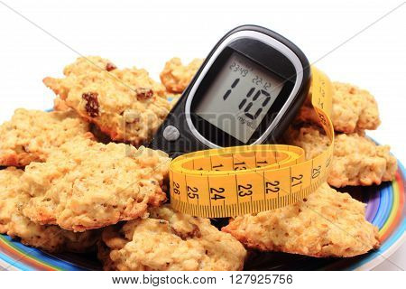 Glucometer oatmeal cookies and tape measure lying on colorful plate concept for diabetes slimming and healthy nutrition. Isolated on white background