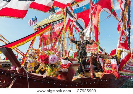 Semporna Sabah Malaysia - Apr 23 2016 : Bajau lady dancing on traditional Bajau boat called Lepa Lepa decorated with colorfull main sail known as Sambulayang parading during the annual Regatta Lepa Festival in Semporna Sabah. This colorful event and the b