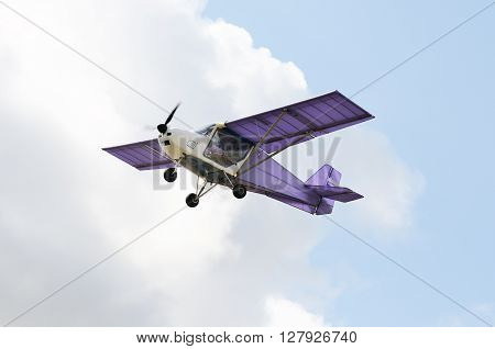 Flying private propeller-driven airplane over cloudy sky