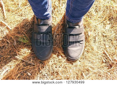 Black leather shoes standing on natural background top view