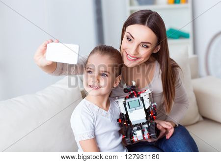 Say cheese. Cheerful pleasant mother holding cellphone and making selfies while playing with her daughter
