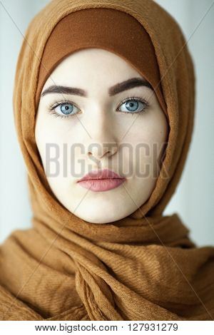 studio portrait of a young women from the eastern face of the traditional Muslim headdress