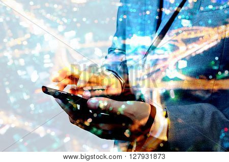 Double Exposure Of Businessman Swipe Mobile Smartphone With Night City