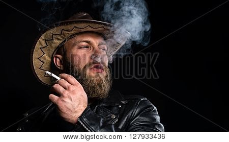 Man In Cowboy Hat With A Cigarette In His Hand