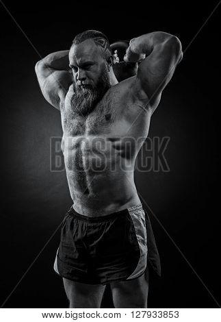 Bodybuilder With A Beard Lifts A Heavy Kettlebell