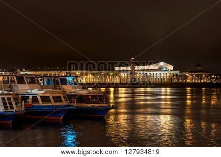 View on Vasilevsky Island - Stock Exchange Building and Rostral columns. Night Photography. In the foreground walking ships.