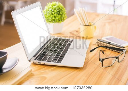 Sideview of wooden office desktop with blank white laptop glasses plant and other items. Mock up