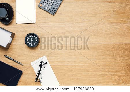 Wooden table with office tools on its left side. Topview Mock up