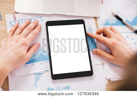 Hands with blank white tablet on wooden desktop with business report on paper sheets. Topview Mock up