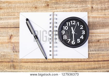 Topview of wooden desktop with black clock notepad and pen