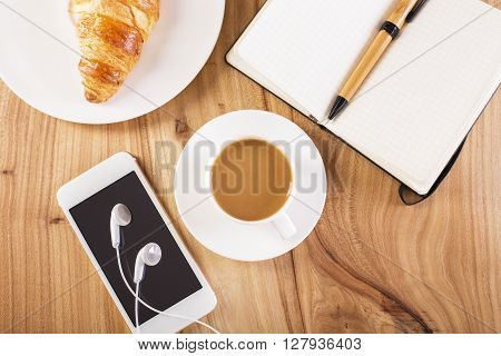 Topview of wooden desktop with coffee croissant phone with headphones and notepad