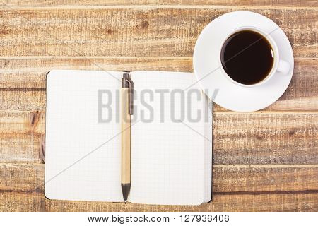 Topview of blank notepad with pen and coffee cup on antique wooden desktop