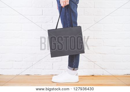 Sideview of female legs with blank shopping bag on white brick wall. Mock up