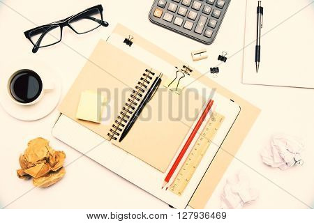 Topview of beige desktop with coffee notepads glasses calculator and other office tools